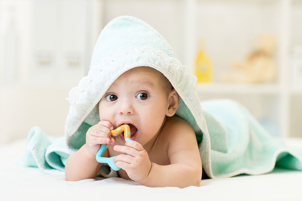 baby wrapped in a towel biting on a teething toy