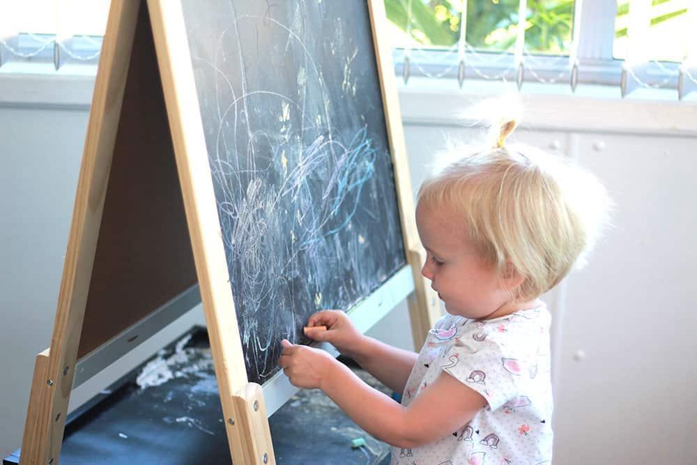 toddler using chalkboard
