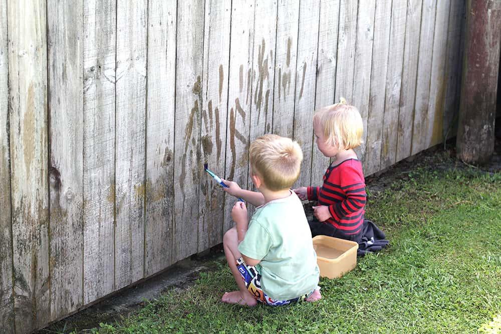 siblings painting fence