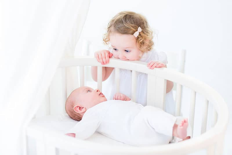 toddler looking at baby in bed
