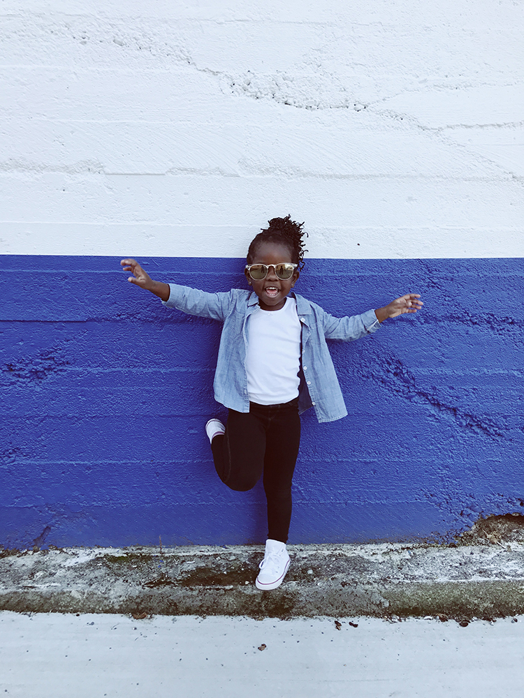 Toddler leaning against bright blue wall