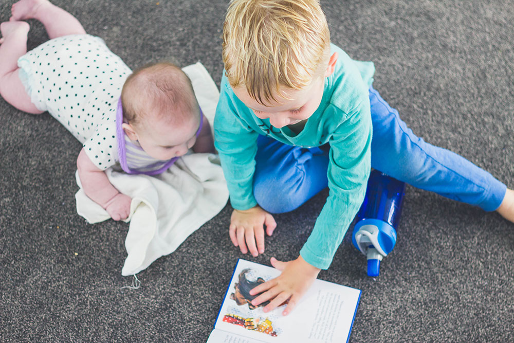 Preschooler reading to 5 month old baby