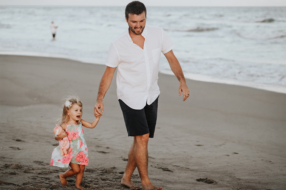 Dad walking on beach with daughter