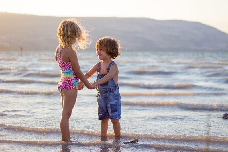 Children on beach holding hands
