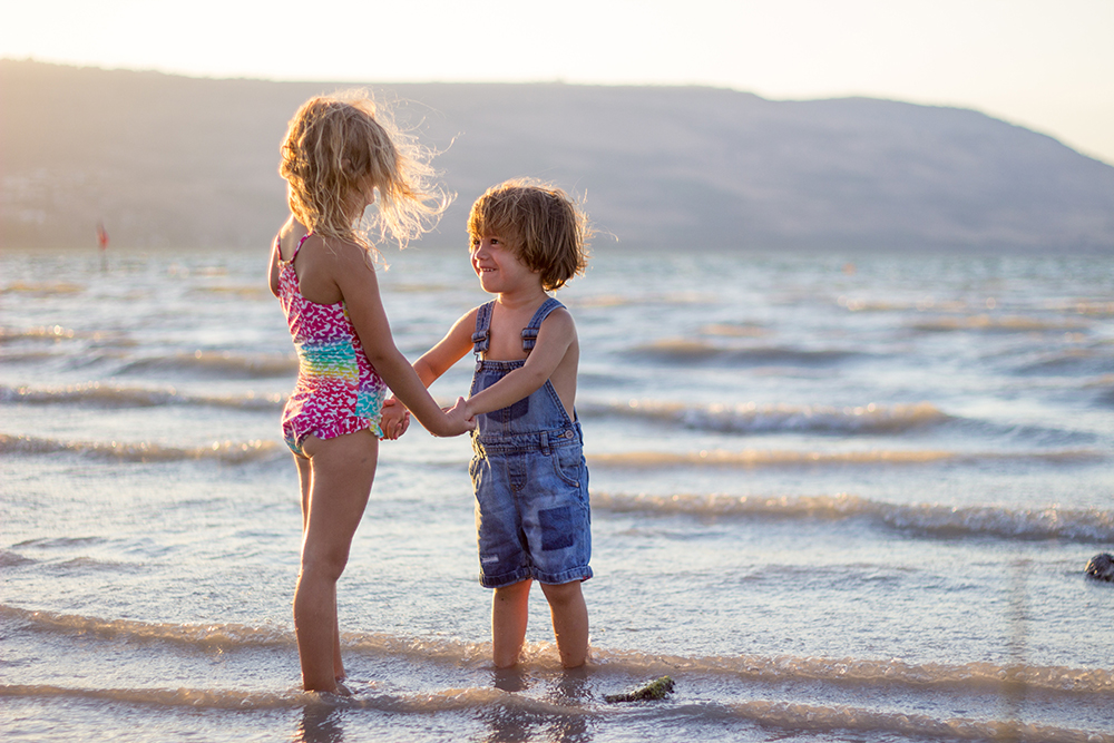 Children on beach holding hands