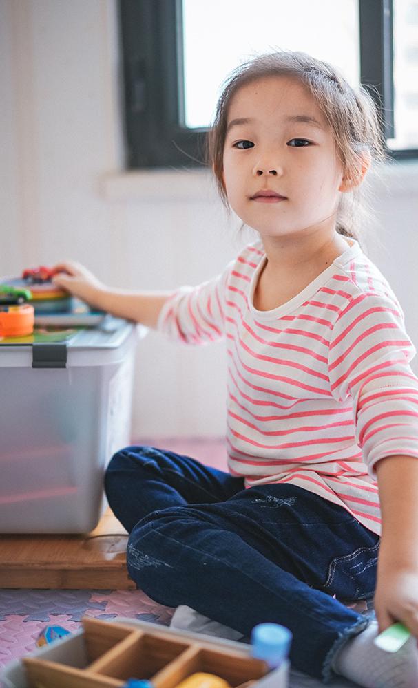 Little girl tidying toys