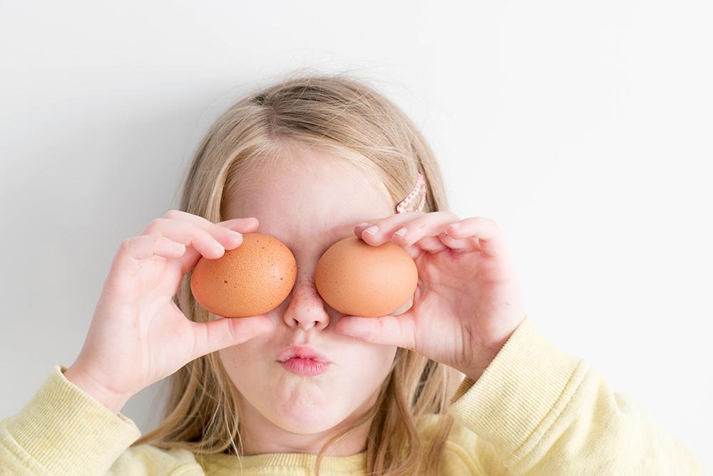 toddler holding chicken eggs